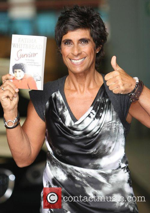 Holding a copy of her book 'Survivor' at...