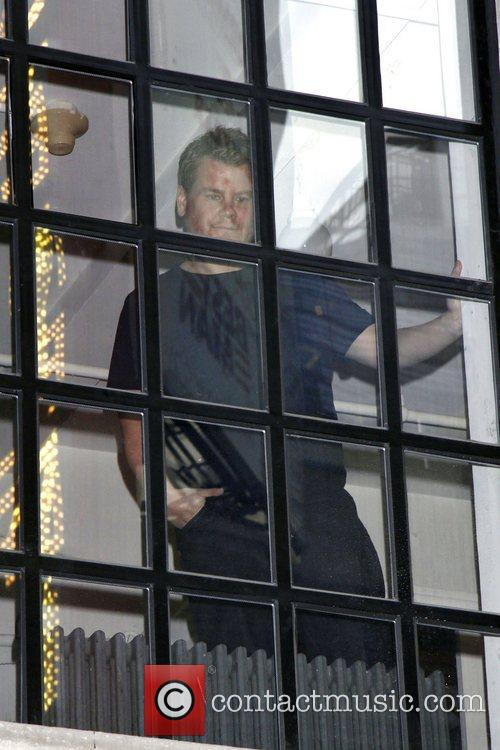 James Corden looking out from a window on...