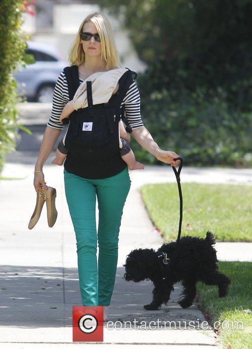 January Jones walks her dog barefoot whilst carrying...