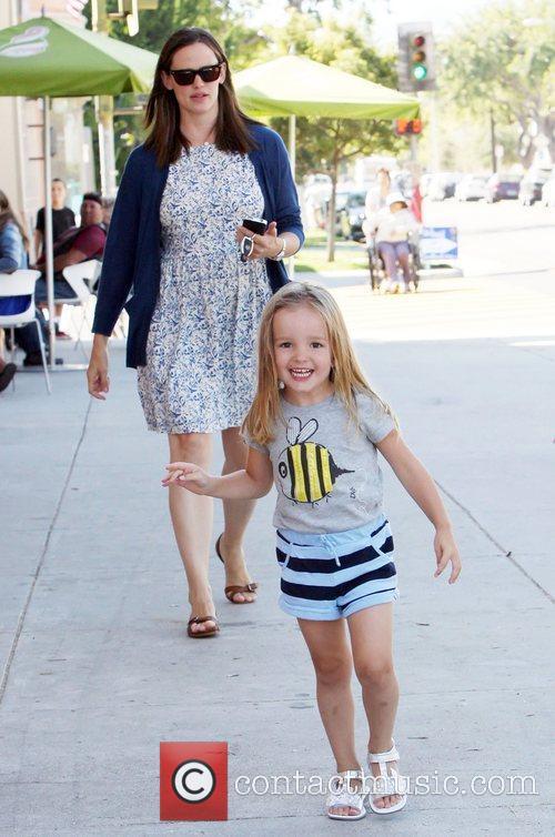 A happy looking Seraphina Affleck playfully runs toward...