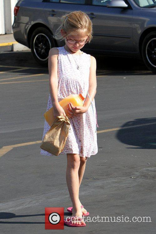 Violet Affleck carries a half-gallon container of orange...