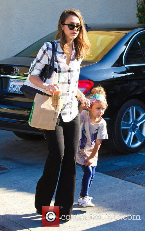 Jessica Alba holds her daughter Honor Marie's hand...