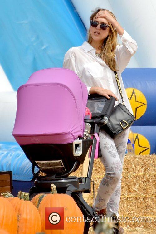 Jessica Alba leaning on her baby daughter's stroller...