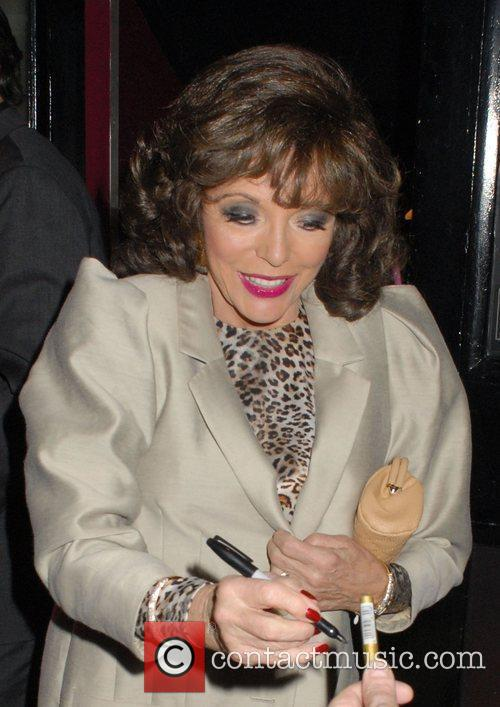 Joan Collins wearing a shoulder padded taupe jacket...