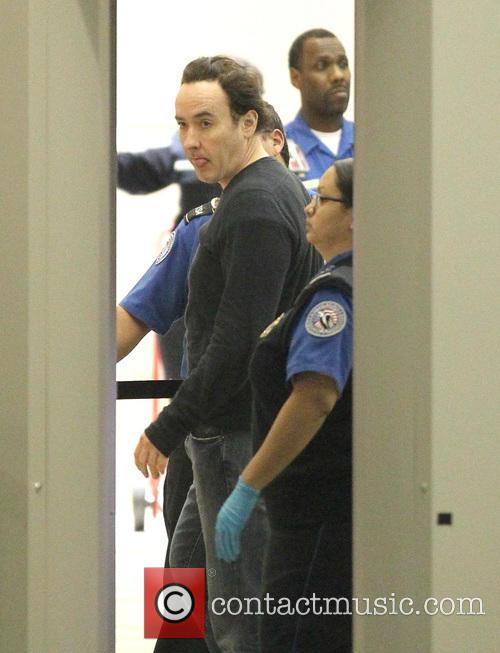 John Cusack goes through the rigorous security search...