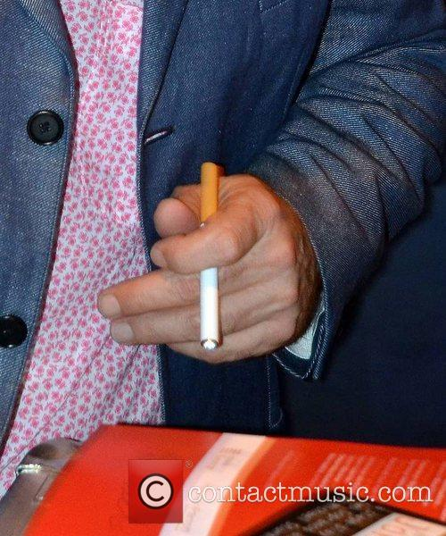 John Malkovich holding an electronic cigarette  as...