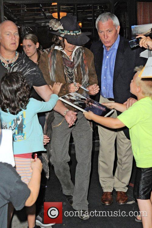 Johnny Depp  surrounded by fans outside the...