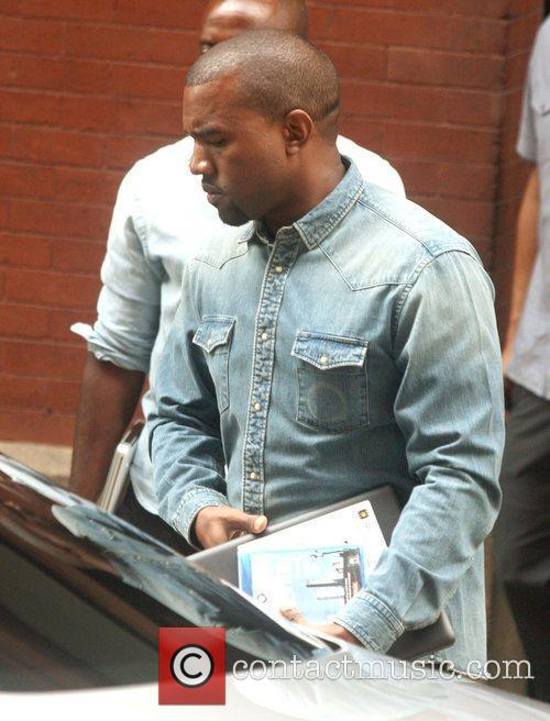 Kanye West in a denim shirt carries a...