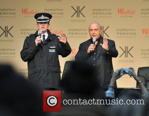 A police officer and Sir Philip Green address...