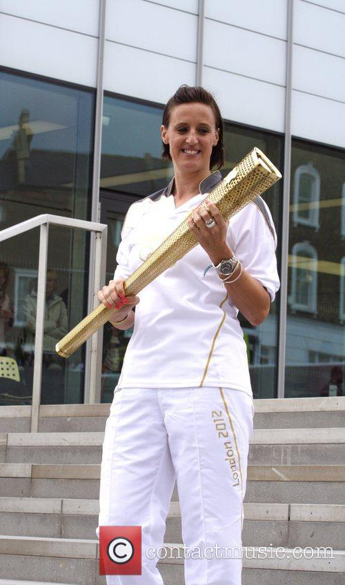 Carries the Olympic Torch on day 62 of...