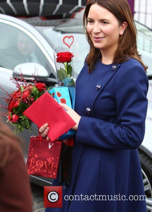 An assistant carries gifts given to Catherine, Duchess...