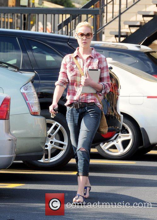 Katherine Heigl carrying her iPad wearing a red...