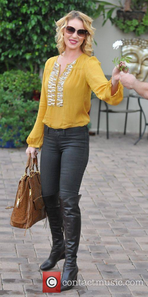 Katherine Heigl  takes a flower from a...