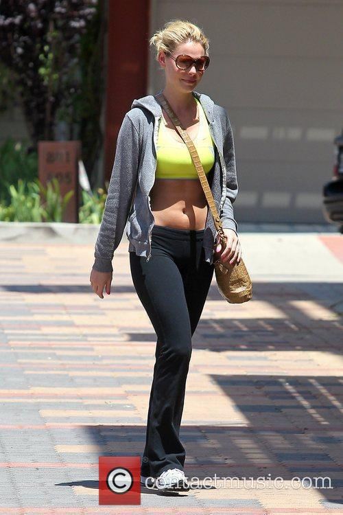 Shows off her bare midriff as she arrives...