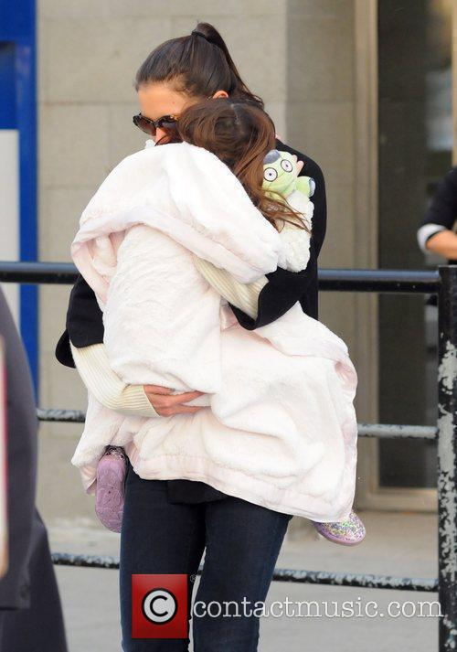 Katie Holmes carries her daughter Suri as they...