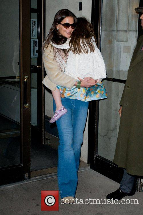 Katie Holmes carries Suri Holmes out of their...