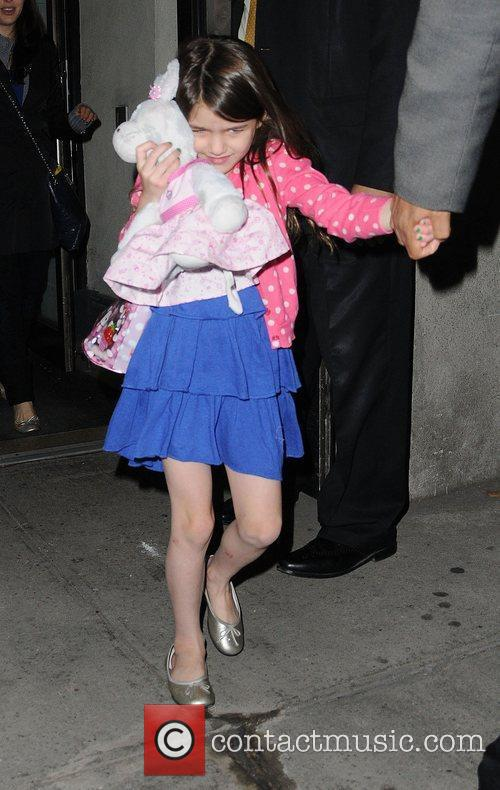 Suri Cruise out and about carrying a cuddly...
