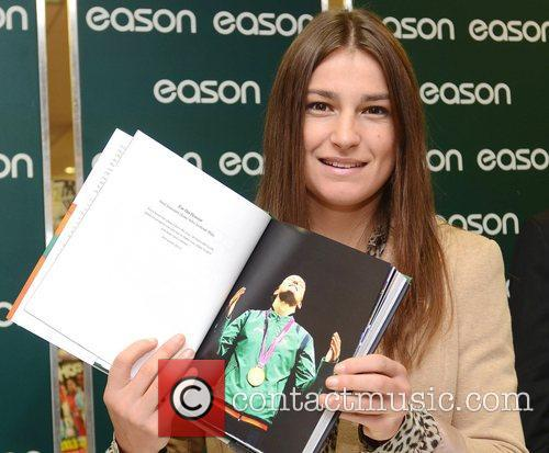 Signs copies of her book entitled 'My Olympic...