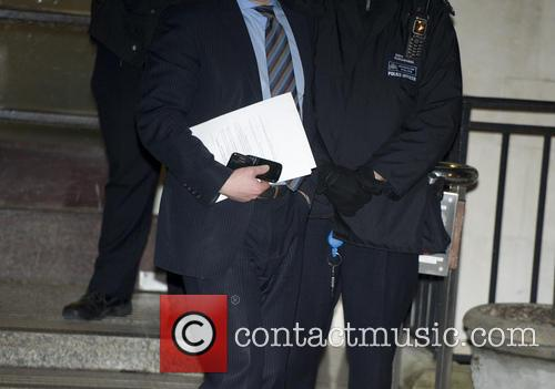 An official carrying a press statement leaves the...