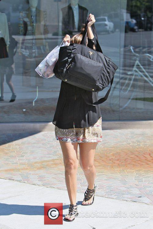 Hides her face with her Prada bag after...