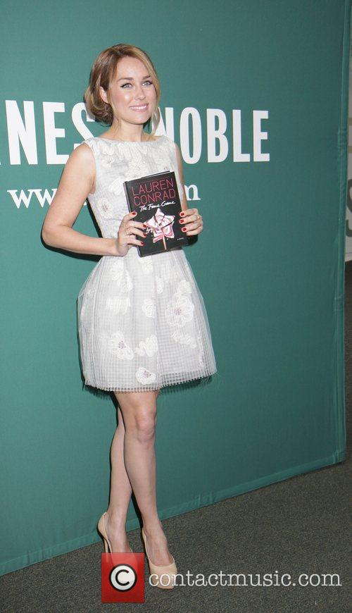 Signs her new book, 'The Fame Game', at...