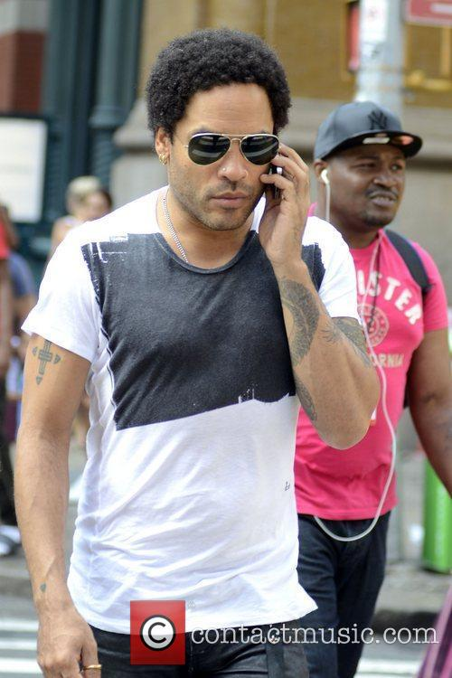 Lenny Kravitz talking on his cell phone as...
