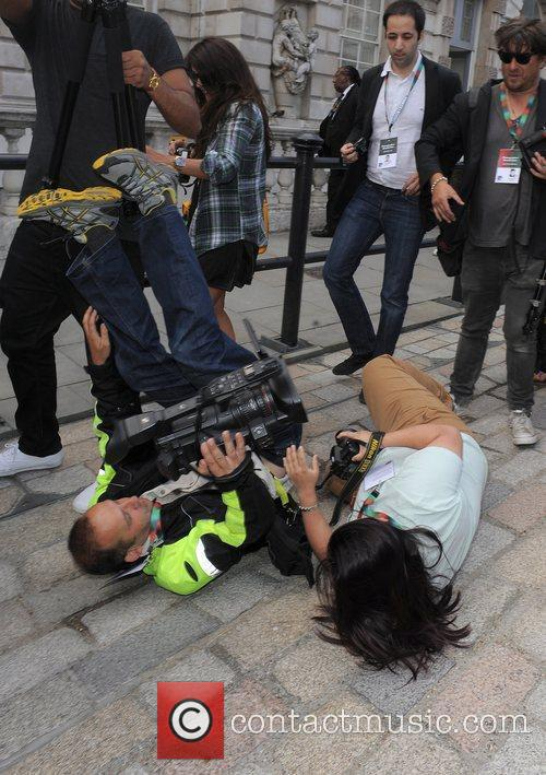 Photographers fall over while trying to take a...