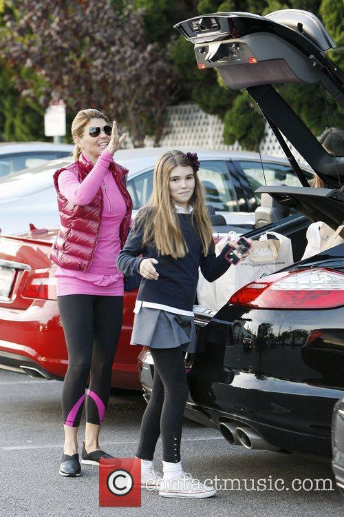 Lori Loughlin returns to her car with daughter...