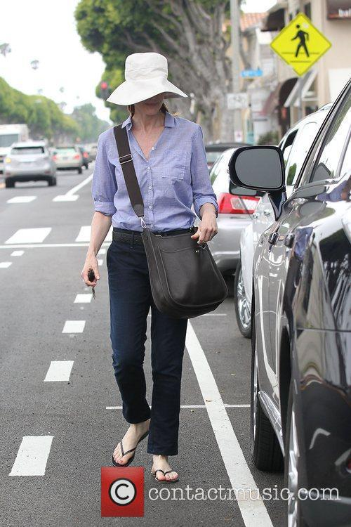 Marcia Cross wearing a large sun hat and...