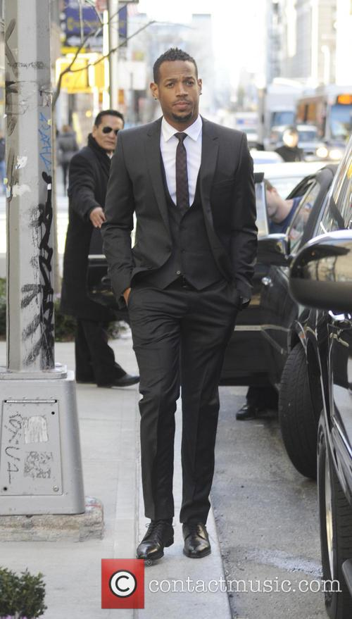 Marlon Wayans leaves a downtown hotel wearing a...