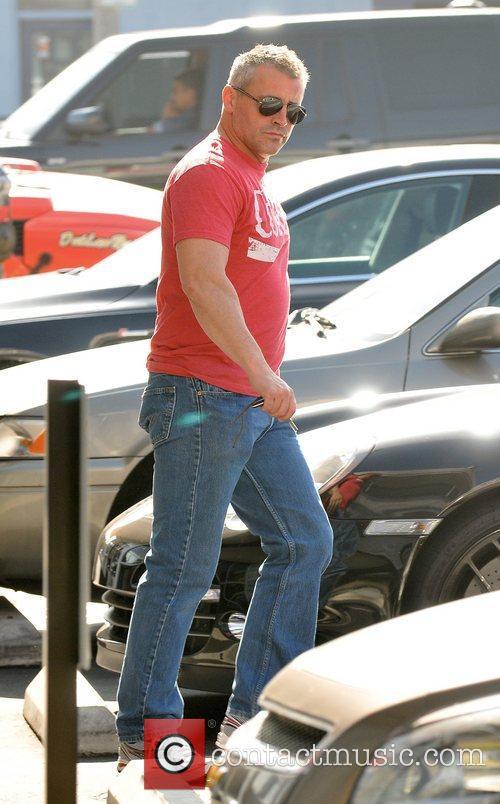 Actor Matt LeBlanc brushes hair off his back...