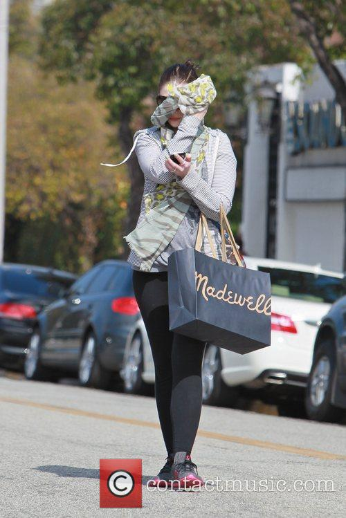 Michelle Trachtenberg hides her face from photographers while...