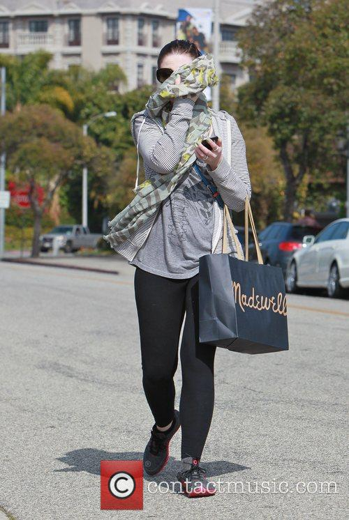 Hides her face from photographers while leaving Byron...