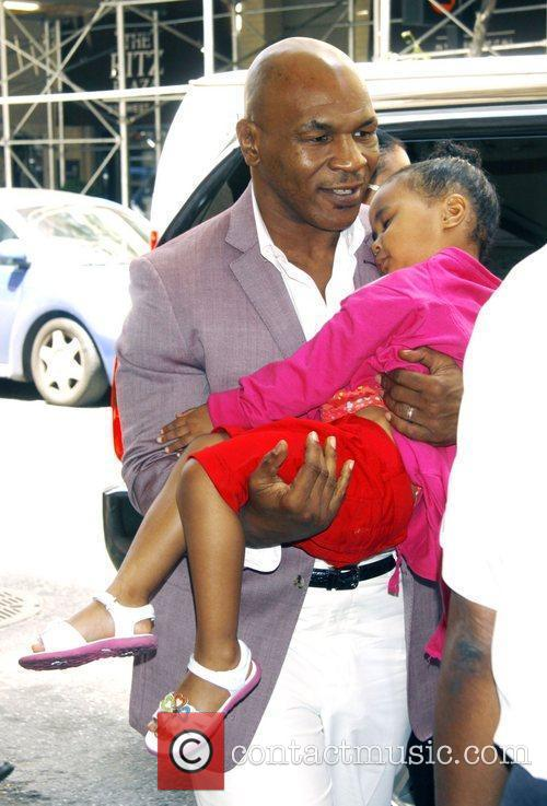 Carries his sleeping daughter, Milan as they leave...