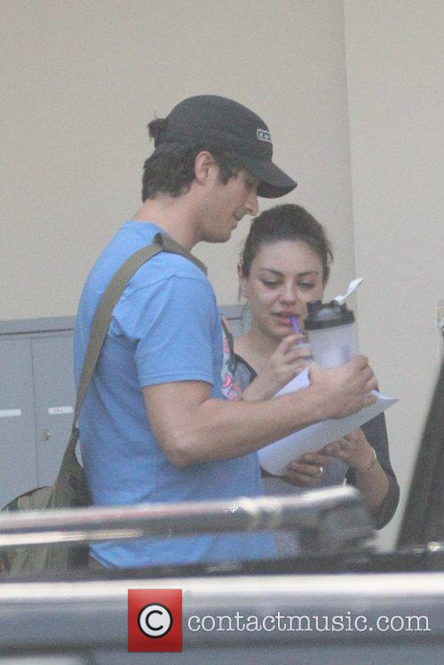 Mila Kunis leaves the gym with her trainer...
