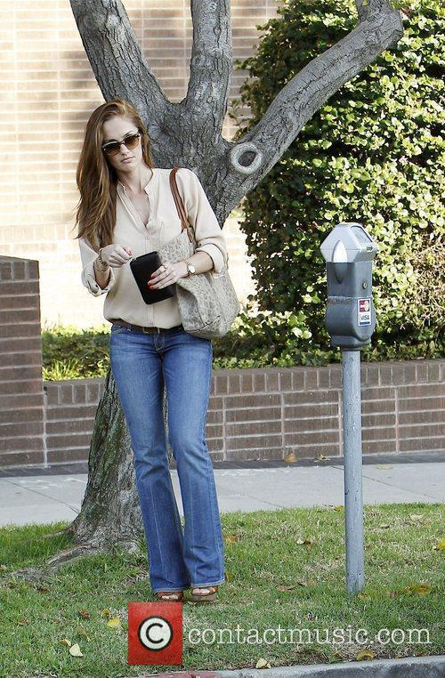 Minka Kelly pays money into a parking meter...