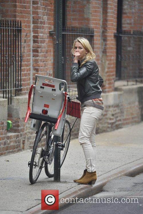 Naomi Watts secures her bicycle to a lamp...