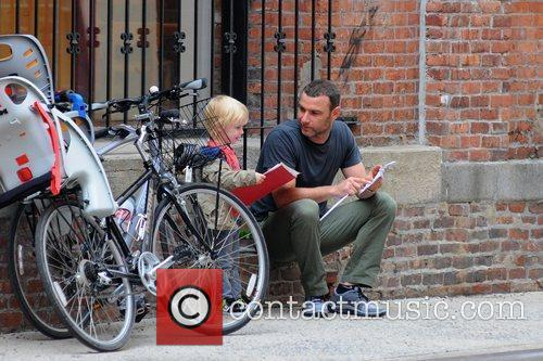 Liev Schreiber reads to his son outside his...