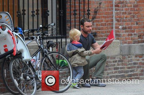 Reads to his son outside his school in...