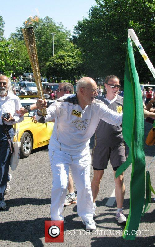 The Olympic Flame is carried through Crystal Palace...