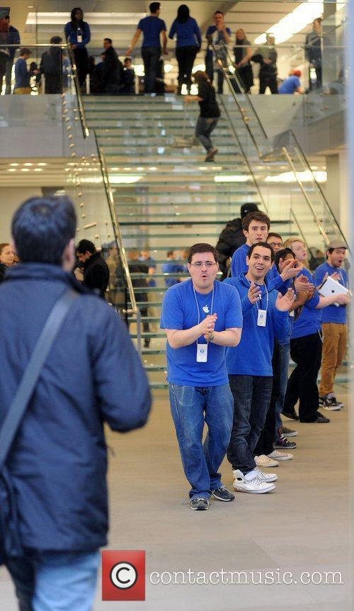 Customers are applauded by Apple staff at the...