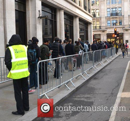 Customers queue outside the Apple store on London's...