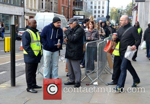 Atmosphere Customers queue outside the Apple store on...
