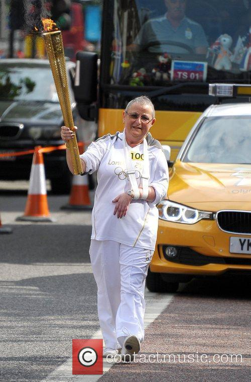 The Olympic Flame is carried through Hackney as...