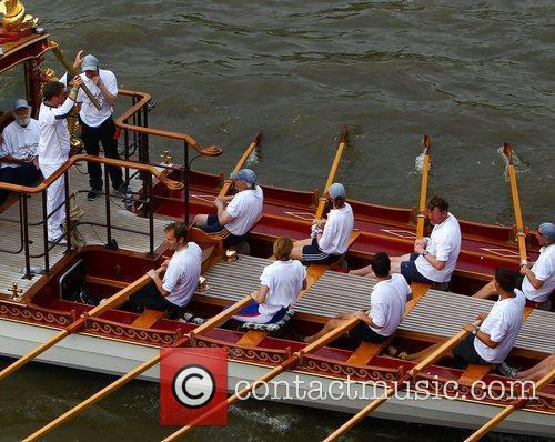 The Olympic torch is rowed along the Thames...