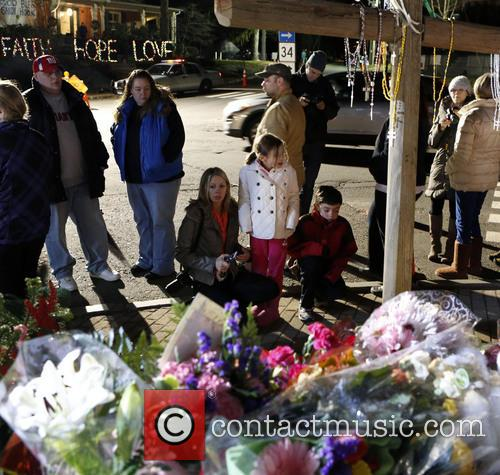 Mourners attend a candlelight vigil at a sidewalk...