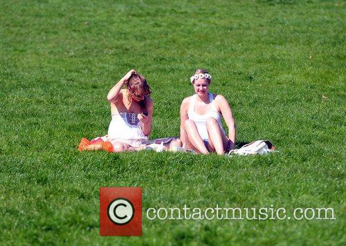 Two young girls enjoying the sunny weather in...
