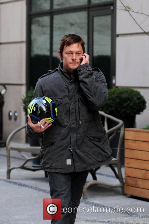 Norman Reedus talking on his cell phone and...