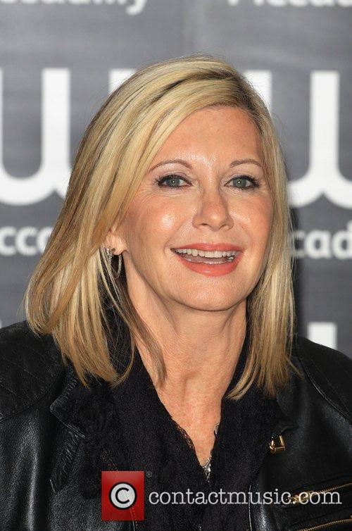 olivia newton john signs copies of her 3835277