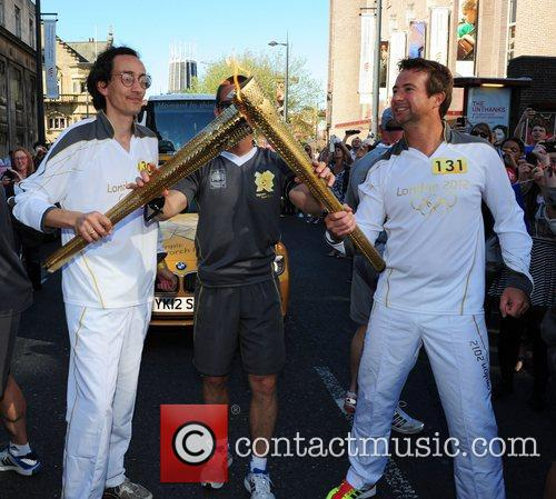 Torchbearer 131 carries the Olympic flame through Liverpool